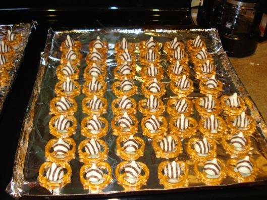Line baking sheet with aluminum foil. Place pretzels on sheet & put a Hug on top of each.