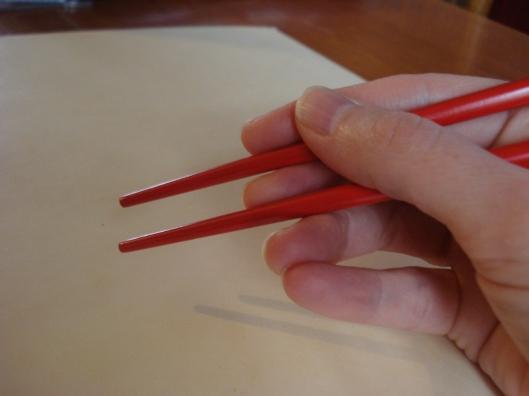Holding chopsticks.
