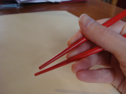 Move only the top chopstick. Keep bottom stationary.