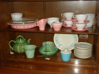 The upper shelf in this pic shows pink and white melamine coffee cups and saucers and a sugar bowl and creamer. The other dishes are NOT melamine. October 2011.