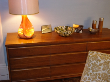 Mid-century lo-boy dresser with orange ceramic lamp and mid-century daisy bowl. February 2012.